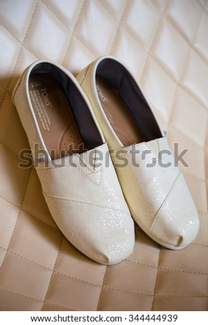 PORTLAND, OR - AUGUST 30, 2014: White leather Toms brand shoes on a patterned chair for the bride to wear during her wedding ceremony. - stock photo