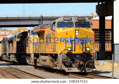 PORTLAND, OR - JULY 14: Union Pacific locomotive and train passes through an industrial section of downtown Portland Oregon on July, 14th, 2013 - stock photo