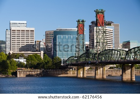 Portland Oregon skyline with Hawthorne bridge crossing the Willamette river under clear blue sky - stock photo