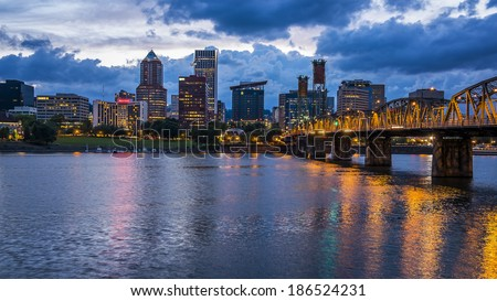 Portland skyline with colorful lights reflecting off the Willamette River at night - stock photo