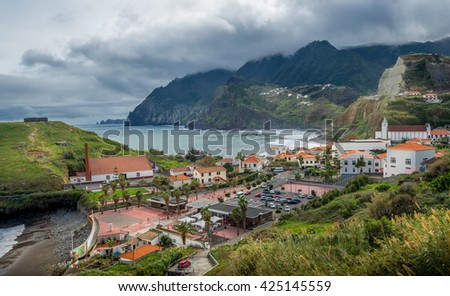Porto da Cruz town in the north shore of Madeira island in stormy weather with mountain range in the heavy clouds. Madeira, Portugal.