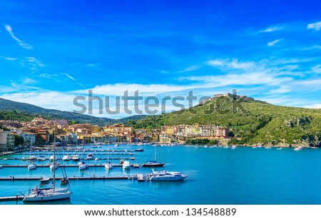 Porto Ercole village and boatd in harbor in a sea bay. Filippo fort on background. Aerial view. Monte Argentario, Tuscany, Italy - stock photo