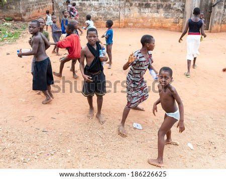 PORTO-NOVO, BENIN - MAR 10, 2012: Unidentified Beninese children play in the street in the street. People of Benin suffer of poverty due to the difficult economic situation - stock photo