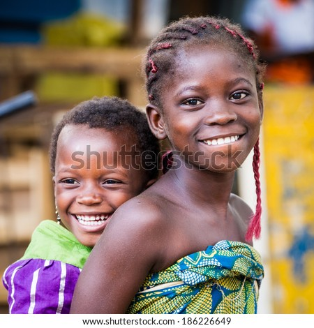 PORTO-NOVO, BENIN - MAR 10, 2012: Unidentified Beninese girl carries her little sister smiling in a colorful dress. People of Benin suffer of poverty due to the difficult economic situation - stock photo