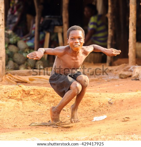 PORTO-NOVO, BENIN - MAR 8, 2012: Unidentified Beninese little boy jumps imitatiing a duck. People of Benin suffer of poverty due to the difficult economic situation.