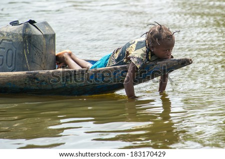 PORTO-NOVO, BENIN - MAR 9, 2012: Unidentified Beninese little girl bored in a wooden boat. People of Benin suffer of poverty due to the difficult economic situation.