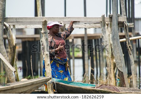 PORTO-NOVO, BENIN - MAR 9, 2012: Unidentified Beninese woman in a red hat with a fish net in a wooden boat. People of Benin suffer of poverty due to the difficult economic situation.