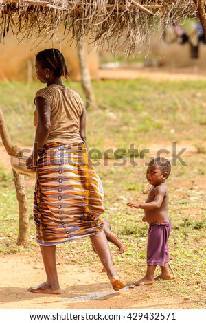 PORTO-NOVO, BENIN - MAR 8, 2012: Unidentified Beninese woman plays with her children. People of Benin suffer of poverty due to the difficult economic situation.