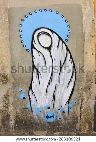 PORTO, PORTUGAL - APRIL 26, 2015: Virgin Mary by graffiti artist Hazul Luzah. Hazul incorporates the Virgin Mary image in many of his works. - stock photo