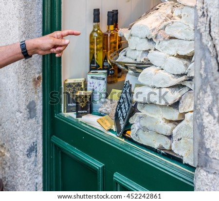 Porto, Portugal - June 24, 2016. Finger pointing a storefront full of raw, dried and salted cod in Porto, Portugal. - stock photo