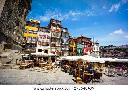 PORTO, PORTUGAL - JUNE, 11: Tourists visit restaurants at famous place Ribeira Square on June 11, 2015 in Porto, Portugal - stock photo