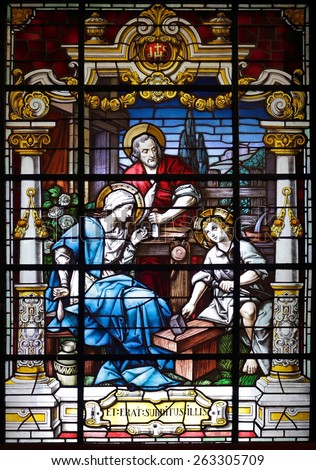 Porto, Portugal - March 23, 2015: Stained glass window from  church of Lapa representing a scene of the holy family, seeing Jesus learning carpentry, the office of the adoptive father, St. Joseph - stock photo