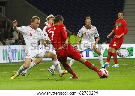 PORTO, PORTUGAL - OCTOBER 8: Cristiano Ronaldo (POR) dribles Lars Jacobsen (DEN) in the Euro 2012 Group Stage Qualifying match against Denmark on October 8, 2010 in Porto, Portugal - stock photo
