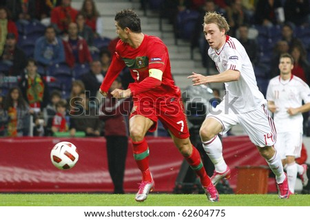 PORTO, PORTUGAL - OCTOBER 8: Cristiano Ronaldo (POR) escapes with the ball from Christian Eriksen (DEN) in the Euro 2012 Qualifying match against Denmark on October 8, 2010 in Porto, Portugal - stock photo