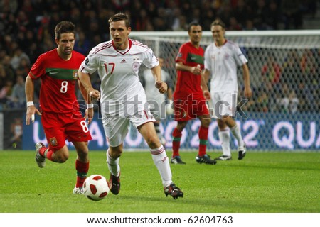 PORTO, PORTUGAL - OCTOBER 08: Peter Lovenkrands (DEN) protecting the ball from Joao Moutinho (L) (POR) in the Euro 2012 Qualifying match on October 8, 2010 in Porto, Portugal - stock photo