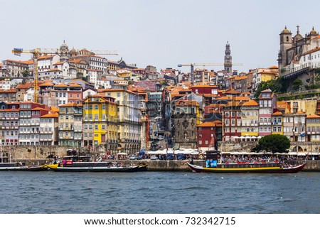 PORTO, PORTUGAL, on June 17, 2017. The sun lights the embankment on the opposite bank of the river of Douro. People and cars move on the embankment. Authentic boats are moored at pier