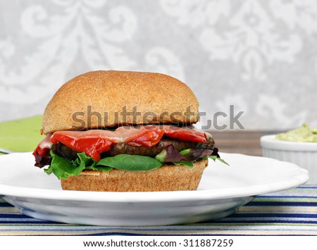 Portobello mushroom burger on a whole wheat roll with roasted peppers, basil,  provolone cheese and greens.  Close up with copy space.