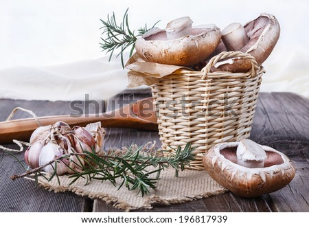 Portobello mushrooms in a woven basket, garlic and rosemary over rustic wooden background. Selective focus - stock photo