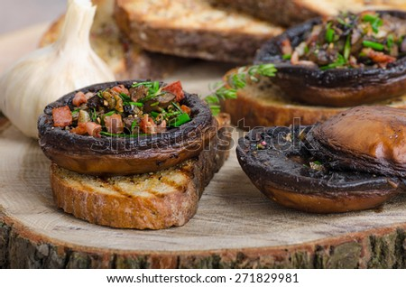 Portobello stuffed with herbs, bacon and garlic, delicacyon toasted crusty garlic bread - stock photo