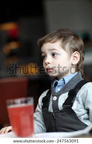 Portrail of thinking child with red juice in the cafe - stock photo