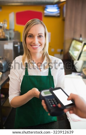 Portrairt of female worker accepting payment from customer through NFC in bakery - stock photo