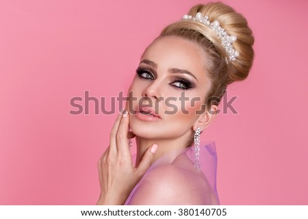 portrait a beautiful young woman, princess, ballerina in  elegant bun with long blond hair and the embellishment of pearls, diamond earrings, she has a beautiful ,perfect face and amazing eyes, makeup - stock photo