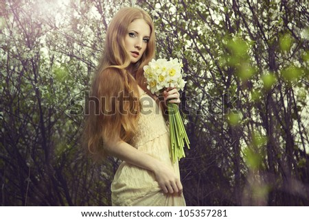 Portrait a beautiful young woman with flowers in the garden. Fashion photo - stock photo