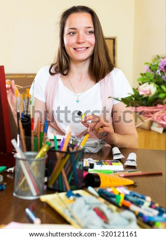 Portrait a cheerful young artist paints a picture at home - stock photo