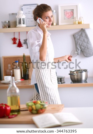 Portrait a smiling woman with phone  of vegetables in kitchen at home