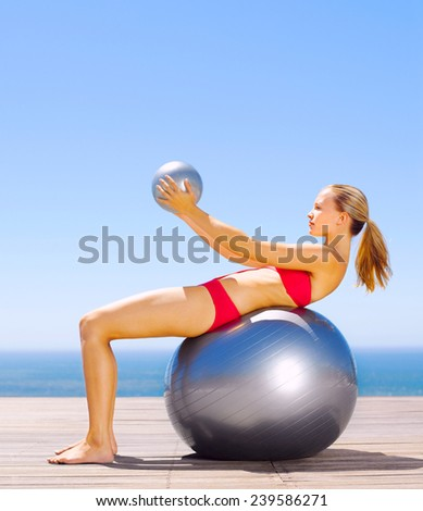 Portrait active and fit attractive looking mature woman at beach doing stretch exercises with gymnastic ball - stock photo
