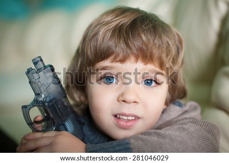 portrait amazing beautiful  happy smiling fun little boy  big blue eyes and long eyelashes play with toy gun creative studio background natural - stock photo