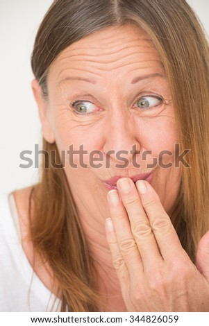 Portrait amused attractive mature woman with funny laughing facial expression, covering mouth with hand, bright background. - stock photo