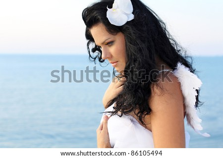 Portrait angel woman wearing angelic wings over white, outdoors - stock photo