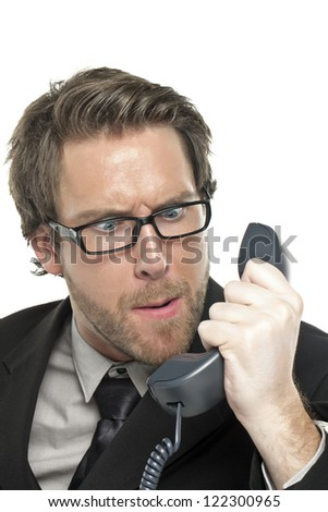 Portrait angry businessman looking to the phone against white background - stock photo