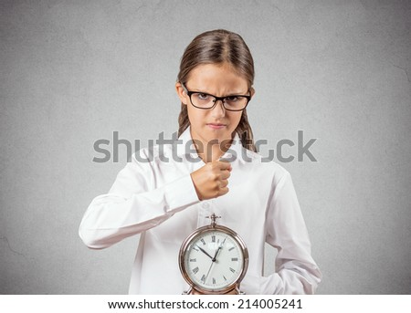 Portrait angry, mad, pissed off teenager girl pretending to be boss manager about to smash alarm clock with fist isolated grey wall background. Negative human emotion facial expression strict attitude - stock photo