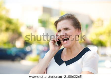 Portrait Angry Woman Screaming while Talking on mobile Phone, isolated outdoors parking lot background. Negative human emotions, facial expressions, feelings, attitude. Bad communication concept - stock photo