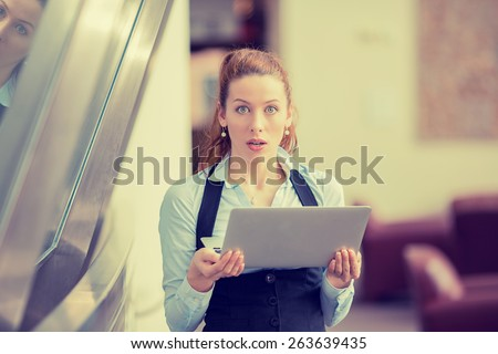 Portrait anxious young girl looking at camera seeing bad news or photos on computer, disgusting shocked emotion on her face isolated office windows background. Human emotion, reaction, expression - stock photo