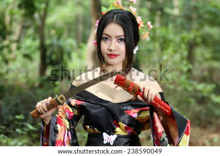 portrait Asia Beautiful Japanese kimono woman and Japanese geisha woman with Japanese sword and Woman with japan sword katana in hands - stock photo