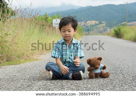 portrait Asian boy sitting on Mountain Road with brown teddy bear doll,vintage picture style,alone boy  - stock photo