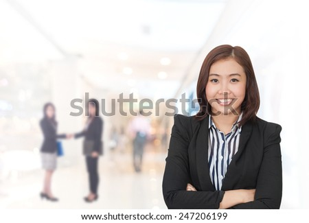 portrait asian businesswoman 20 - 30 year old with long hair has shopping mall background.Mixed Asian / Caucasian businesswoman.Positive emotion