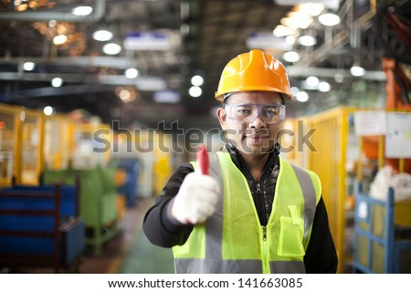 Portrait asian engineer showing thumb up in factory - stock photo