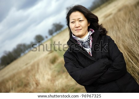 Portrait asian woman looking at camera in the field - stock photo