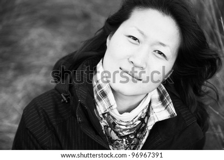 Portrait asian woman looking up camera in the field - stock photo