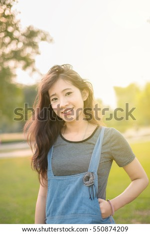 Portrait asian woman smiling happy freedom in park with sunlight