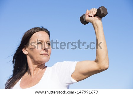 Portrait attractive confident mature woman exercising with weights, keeping healthy and fit, focused view, determined, positive, successful, with blue sky as background and copy space. - stock photo