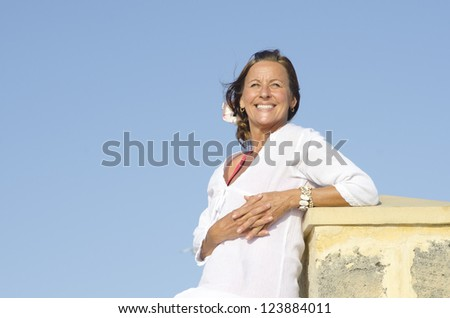 Portrait Attractive happy middle aged woman posing relaxed outdoor, enjoying active retirement, isolated with blue sky as background and copy space. - stock photo