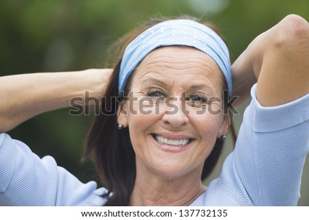 Portrait attractive looking mature woman cheerful, joyful happy smiling outdoor, wearing blue shirt and headband, arms behind neck, blurred background. - stock photo