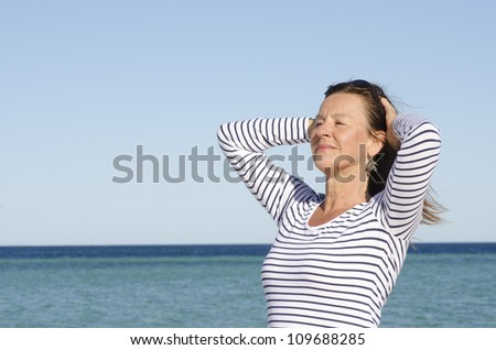 Portrait attractive looking mature woman posing relaxed at seaside holiday, isolated with ocean and blue sky as background and copy space.