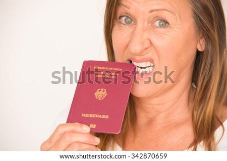 Portrait attractive mature woman biting upset, angry, worried German passport document, bright background. - stock photo