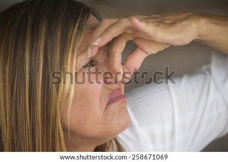 Portrait attractive mature woman feeling unhappy, annoyed about smelly, polluted air, squeezing nose with fingers, blurred background, copy space. - stock photo